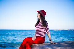 Atrakcyjna kobieta w czerwonym obsiadaniu nad błękitnym niebem i morzem Fotografia Royalty Free