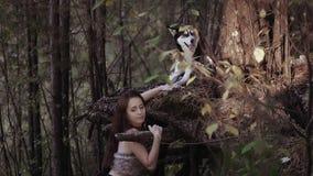 Atrakcyjna kobieta w etnicznej odzieżowej pozyci w zwartym lesie pod ogromni drzewa i mienie pies jest łapą zbiory