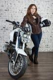 Atrakcyjna kobieta w rocznika stroju trzyma białego hełm, stoi blisko motocyklu, ściana z cegieł tło zdjęcia stock