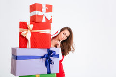 Atrakcyjna kobieta w Santa Claus kostiumu chuje za teraźniejszymi pudełkami Obraz Stock