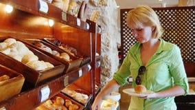 Atrakcyjna kobieta wybiera chleb przy kawiarnią z samoobsługą zbiory
