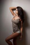 Atrakcyjna kobieta z długie włosy w odgórnych i białych majtasach pozuje blisko szarości ściany Boczny widok perfect ciało kobiet Fotografia Stock
