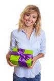 Atrakcyjna kobieta z kędzierzawym blondynem i urodzinowym prezentem Fotografia Royalty Free