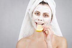 Atrakcyjna kobieta z twarzową maską na jej twarzy trzyma cytrus owoc w jej ręce na białym tle Fotografia Royalty Free