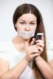 Atrakcyjna kobieta z usta pieczętującym no może opowiadać na telefonie komórkowym, popielaty tło Obrazy Royalty Free