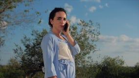 Atrakcyjna kobiety brunetka w Błękitnym kostiumu Z używa telefon komórkowy Biznesowej kobiety use telefon kom?rkowy zbiory