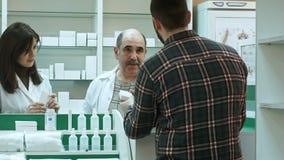 Atrakcyjna kobiety i seniora farmaceuta słucha męski klient dissapointed medycyny ilość rozwiązywać próba i Zdjęcia Royalty Free