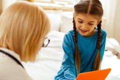 Atrakcyjna lekarka oferuje pastylkę dziewczyna z warkoczami obraz stock
