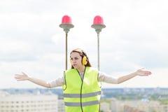 Atrakcyjna śliczna pracownik kobieta w zielonym zachodu i earmuffs stojaku na dachu, chwyt pastylka Obrazy Stock