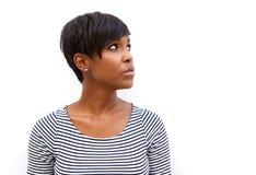 Atrakcyjna młoda amerykanin afrykańskiego pochodzenia kobieta patrzeje daleko od Fotografia Stock