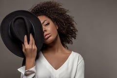 Atrakcyjna młoda amerykanin afrykańskiego pochodzenia kobieta w białym koszulowym mienie czarnym kapeluszu nad połówką jej twarz zdjęcie stock