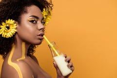 Atrakcyjna młoda amerykanin afrykańskiego pochodzenia kobieta z artystycznym makijażem i gerberas w włosianym pije mleku od butel zdjęcia stock