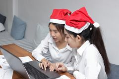 Atrakcyjna młoda Azjatycka biznesowa kobieta w Santa kapeluszach używać laptop w biurze Boże Narodzenia lub mas pojęcie Selekcyjn Obrazy Royalty Free