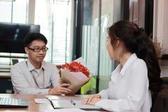 Atrakcyjna młoda Azjatycka kobieta akceptuje bukiet czerwone róże od chłopaka w biurze na valentine ` s dniu Miłość i romans w wo Fotografia Stock