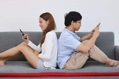 Atrakcyjna młoda Azjatycka para używa mobilnego mądrze telefon wpólnie w żywym pokoju Internetowy technologia stylu życia pojęcie obraz royalty free