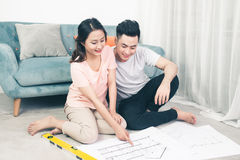Atrakcyjna młoda azjatykcia dorosła para patrzeje domowych plany Obraz Royalty Free
