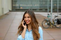 Atrakcyjna młoda biznesowa kobieta opowiada na jej telefonie podczas gdy stojący w podwórzu biurowi bloki Rozochocona biznesowa k Zdjęcie Royalty Free