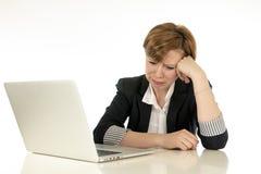 Atrakcyjna młoda biznesowa kobieta pracuje na jej komputerze stresującym się, męczącym i przytłaczającym, smutny Zdjęcia Stock