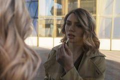 Atrakcyjna Młoda blondynki kobieta w okopu odprowadzeniu w miast lustrach z rocznik walizką Zdjęcia Stock