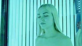 Atrakcyjna młoda blondynki kobiety pozycja w skórniczy budka z jej oczami zamykającymi fotografia stock