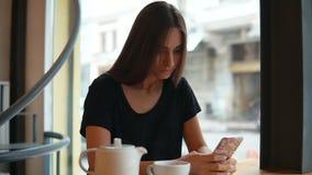 Atrakcyjna młoda dama z naturalnym makeup używać jej telefon komórkowego w sklep z kawą Nowożytny przyrządu użycie na zakupy zbiory wideo