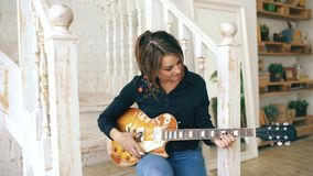 Atrakcyjna młoda dziewczyna uczy się bawić się gitarę elektryczną siedzi na schodkach w sypialni w domu Obrazy Stock