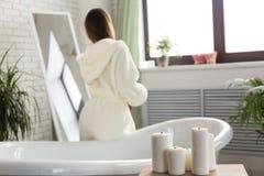 Atrakcyjna młoda dziewczyna w białego bathrobe zgrzywionej włosianej pozycji przed lustrem we wnętrzu łazienki zdjęcie stock