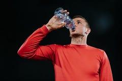 Atrakcyjna młoda Kaukaska sportowiec woda pitna od butelki patrzeje daleki z rozważnym twarzy wyrażeniem, ubierającym w czerwieni Obrazy Royalty Free