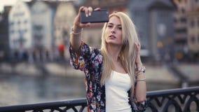 Atrakcyjna młoda kobieta bierze selfie na czarnym mosta krzyżu wodnego kanał, powabnego uśmiech i seksownego spojrzenie, _ zbiory