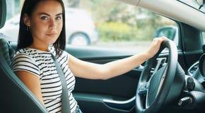 Atrakcyjna młoda kobieta jedzie samochód obrazy stock
