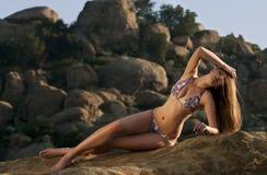 Atrakcyjna młoda kobieta jest ubranym projektanta bikini rozciąganie na skale Zdjęcie Royalty Free