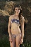 Atrakcyjna młoda kobieta jest ubranym projektanta bikini stojaki przed skałą Obrazy Royalty Free