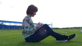 Atrakcyjna młoda kobieta na stadium gazonie używa smartphone na słonecznym dniu zbiory