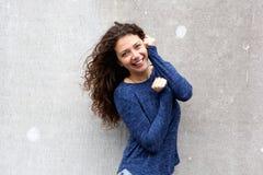 Atrakcyjna młoda kobieta ono uśmiecha się przeciw szarości ścianie Obraz Royalty Free