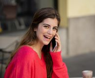 Atrakcyjna młoda kobieta opowiada na jej mądrze telefonie komórkowym w sklepu z kawą tarasie obraz stock
