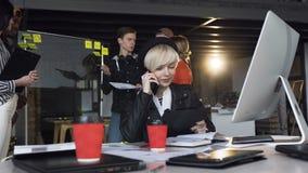 Atrakcyjna młoda kobieta opowiada na mądrze telefonie podczas gdy jej cowoker dyskutuje dane od diagrama na szkło desce zbiory wideo
