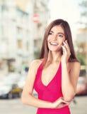 Atrakcyjna młoda kobieta opowiada na telefonie komórkowym Fotografia Royalty Free