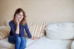 Atrakcyjna młoda kobieta opowiada na telefonie komórkowym i ono uśmiecha się w domu fotografia royalty free