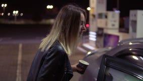 Atrakcyjna młoda kobieta otwiera samochodowego drzwi i siedzi na miejscu pasażera podczas gdy trzymający filiżankę kawy samochodo zdjęcie wideo