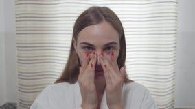 Atrakcyjna młoda kobieta patrzeje w kamerze stosuje dzienną śmietankę na jej twarzy w łazience z heterochromia zdjęcie wideo