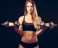 Atrakcyjna młoda kobieta pracująca z dumbbells out - bikini fitne zdjęcie stock