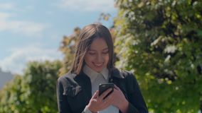Atrakcyjna młoda kobieta przy miasto ulicami pogodnym gawędzeniem z przyjaciółmi i, radosna modniś dziewczyna używa telefon komór zdjęcie wideo