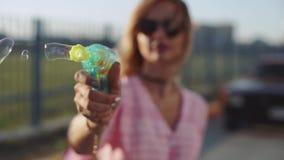 Atrakcyjna młoda kobieta robi mydlanym bąblom od pistoletu przy zmierzchem na ulicie zdjęcie wideo