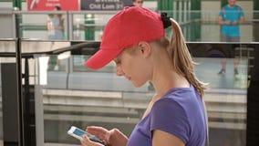 Atrakcyjna młoda kobieta sprawdza jej telefonu czekania pociąg przyjeżdżać na overground metra staci metru zbiory wideo