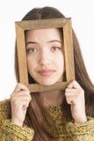 Atrakcyjna młoda kobieta trzyma drewnianą ramę Obraz Royalty Free