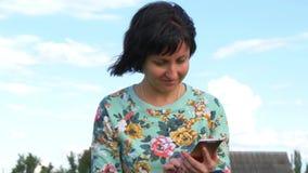 Atrakcyjna młoda kobieta używa smartphone przeciw błękitnemu chmurnemu niebu zbiory
