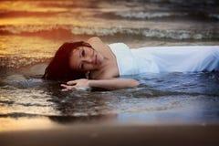 Atrakcyjna młoda kobieta w ślubnej sukni cieszy się wodę morską podczas zmierzchu Zdjęcie Stock