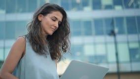 Atrakcyjna młoda kobieta w błękicie smokingowym używać jej laptop w centrum miasta zbiory
