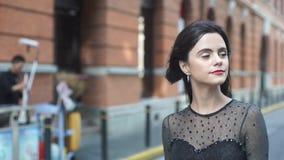 Atrakcyjna młoda kobieta w cudownej sukni chodzi na ulicie zdjęcie wideo