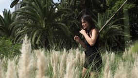 Atrakcyjna młoda kobieta w cudownej sukni chodzi w polu w wysokiej trawie zbiory wideo